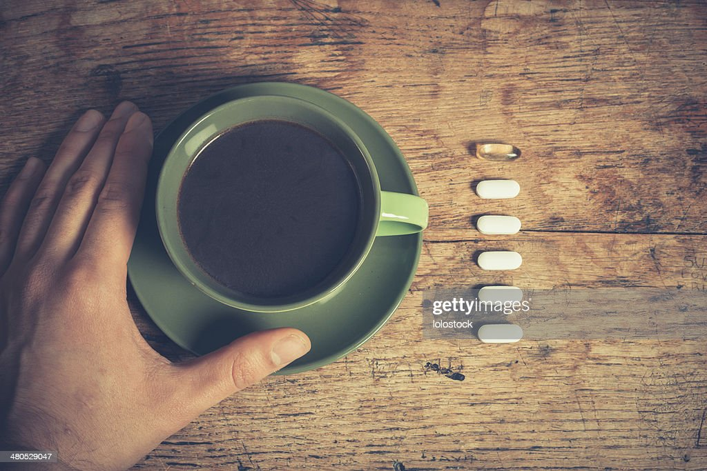 Man having pills and coffee : Stockfoto