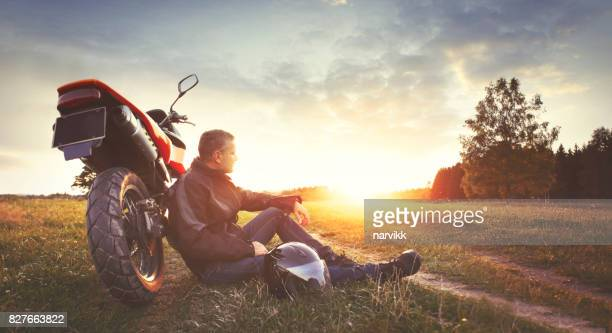Man having rest in the countryside during motorbike trip