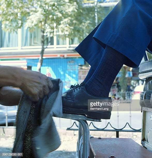 Man having shoes shined outdoors, low section