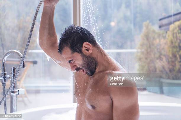 man having shower in a hot tub with a forest view - doccia foto e immagini stock