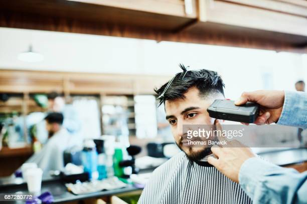 Man having side of head trimmed while having hair cut in barber shop