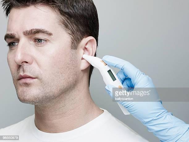 Man Having Temperature Taken in Ear.