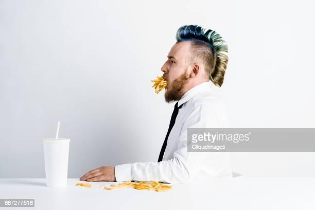 man having unhealthy snack - cliqueimages photos et images de collection