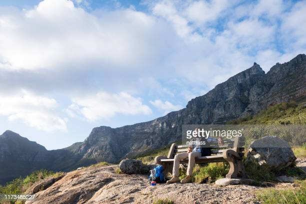man having warm coffee drink while hiking in the mountains - coffee drink stock pictures, royalty-free photos & images