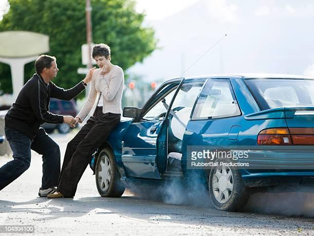 Homem ajudando a mulher após um acidente de Carro