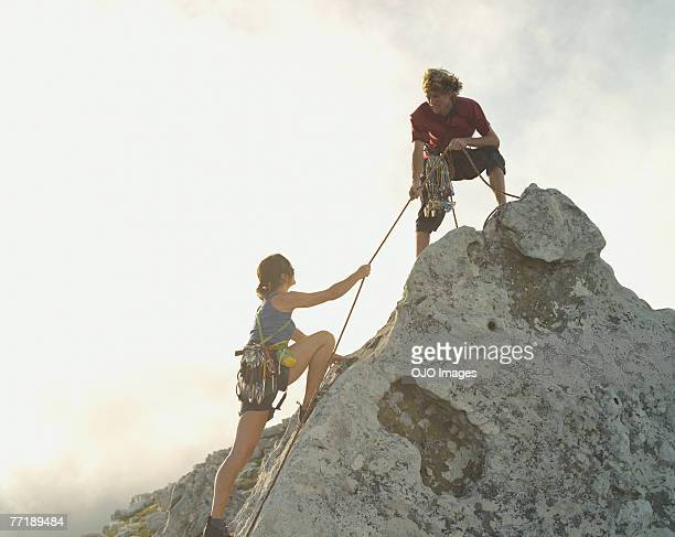 A man helping a woman climber to the top of the mountain