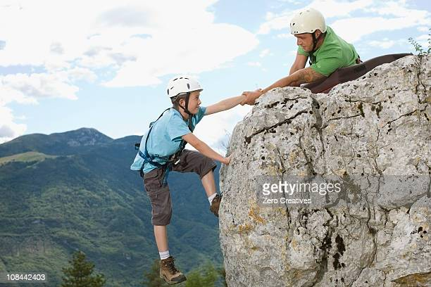 Man helping boy to get to the top