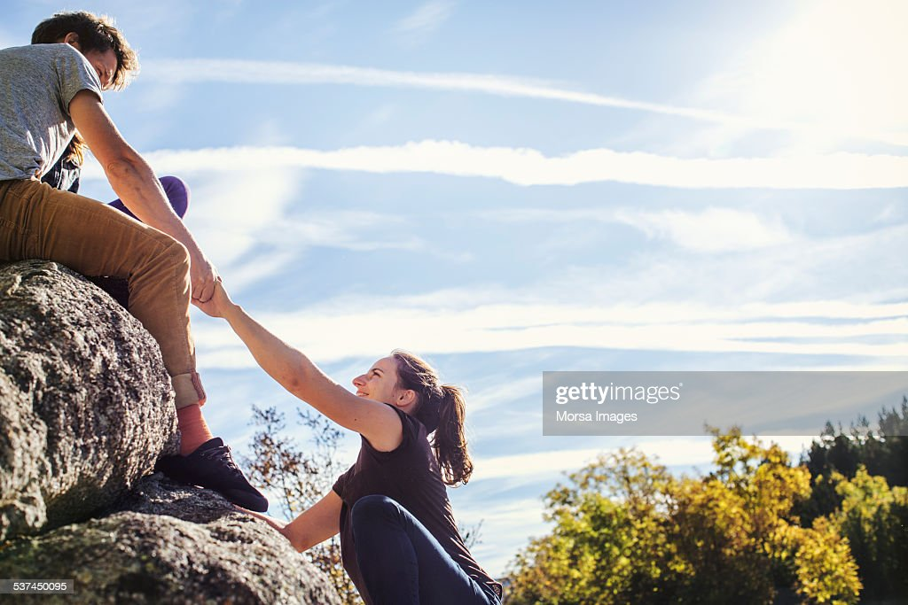 Man helping female friend to climb rock : Stock Photo