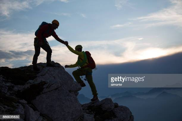 Man helping friend to climb rock mountain
