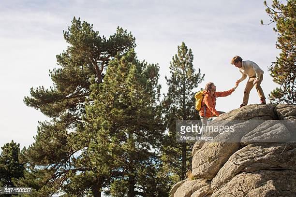 Man helping friend to climb rock