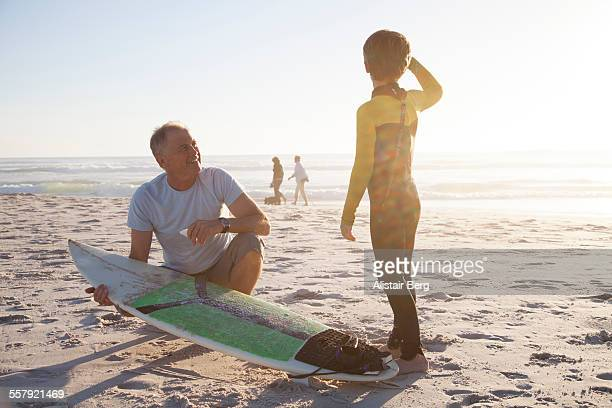 Man helping grandson with surf board