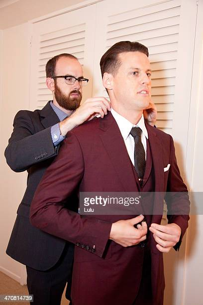 man helping groom put suit jacket on - maroon stock pictures, royalty-free photos & images