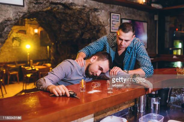 man helping his drunk friend - hangover after party stock pictures, royalty-free photos & images