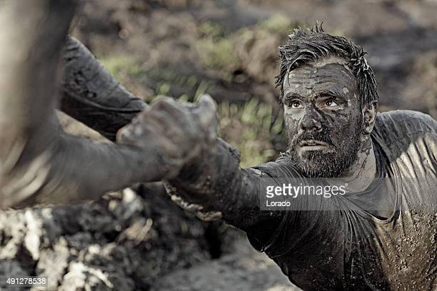 man helping his friend with getting out of mud - obstacle course stock photos and pictures