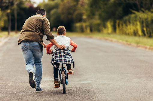 Man helping his kid in learning to ride a bicycle 1140118229