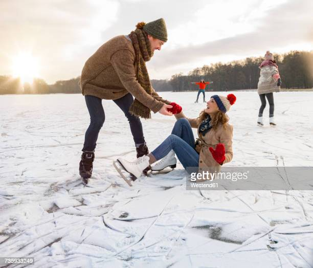 man helping ice skating woman up on icy surface of frozen lake - doing a favor stock pictures, royalty-free photos & images