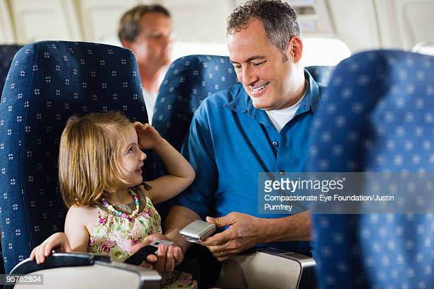 man helping little girl with seat belt - cef do not delete stock pictures, royalty-free photos & images