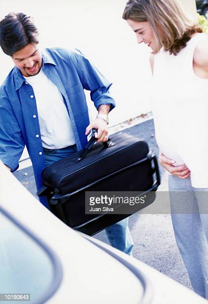 Man helping pregnant woman to car