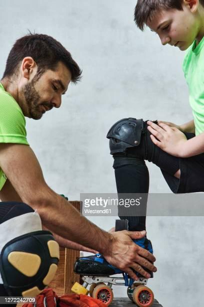 man helping son wearing roller skate before training - caneleira roupa desportiva de proteção imagens e fotografias de stock