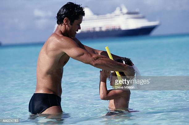man helping son with snorkel and mask - speedo boy stock photos and pictures