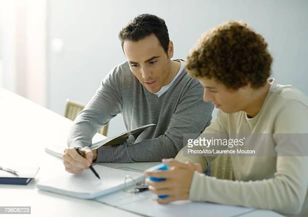 Man helping teenage son with homework