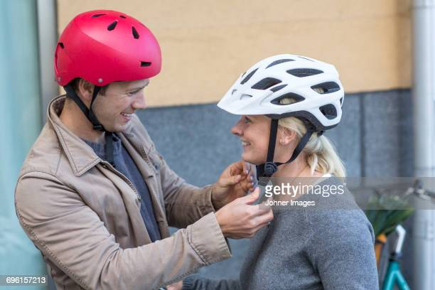 man helping to his girlfriend to fit cycling helmet - cycling helmet stock photos and pictures
