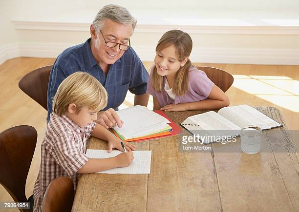 Man helping two kids with homework at kitchen table