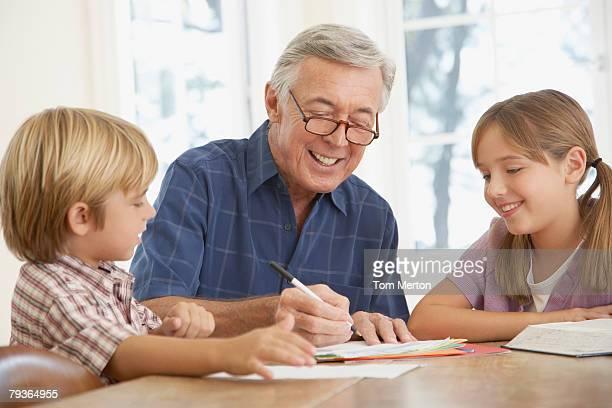 Mann hilft zwei Kindern bei den Hausaufgaben im kitchen table