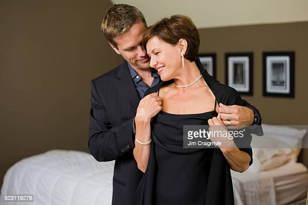 man helping wife with wrap - jim craigmyle stock pictures, royalty-free photos & images