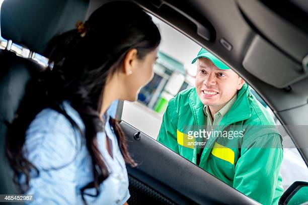 man helping woman at a gas station - station stock pictures, royalty-free photos & images