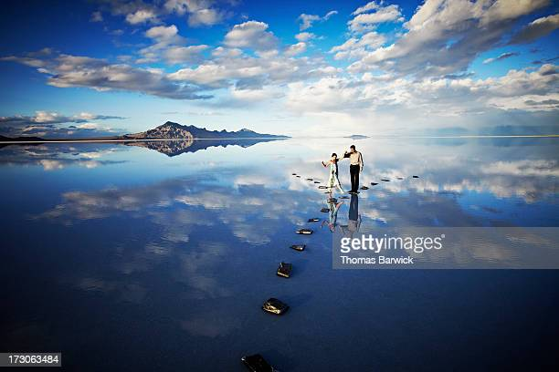 Man helping woman balance on stone pathway in lake