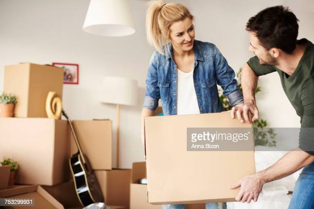 Man helping woman carrying the cardboard box. Debica, Poland