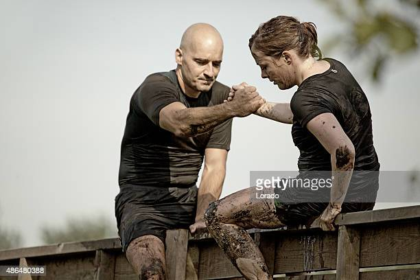 man helping woman to climb wooden wall obstacle - obstacle course stock photos and pictures