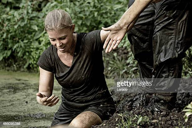 man helping woman to cross an obstacle