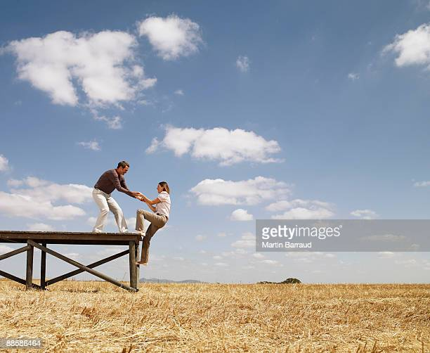 man helping woman up wooden dock in field - pulling stock pictures, royalty-free photos & images