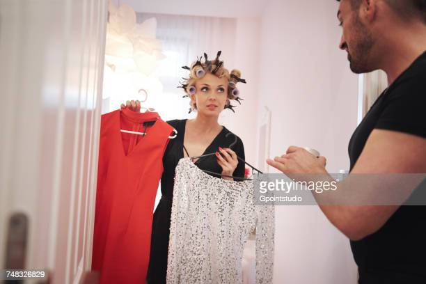 Man helping woman with hair rollers choose dress