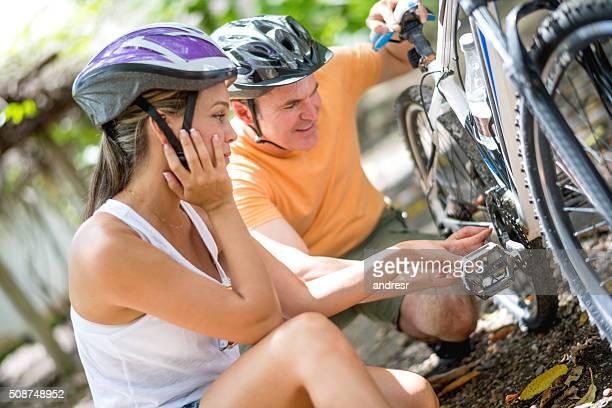 Man helping woman with her broken bike