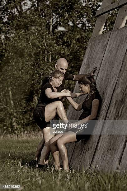 Homme aidant femme à escalader des murs en bois obstacle
