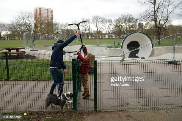 Man helps a child lift his scooter over the fence at the Victoria Park skatepark on March 6, 2021 in London, England. Londoners are enjoying bright...