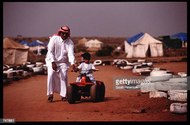 A man helps a child ride a buggy August 15 1997 in Abha Saudi Arabia Near the Red Sea the Asir Mountains are a popular destination for Saudis who...