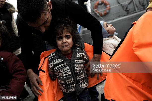 A man helps a girl with her life jacket as migrants and refugees arrive on the Greek island of Lesbos while crossing the Aegean Sea from Turkey on...