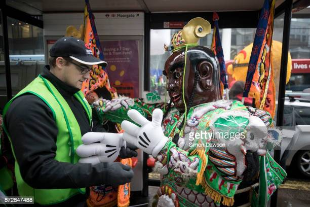 A man helps a performer from Taiwan get into a costume as they prepare to march in the Lord Mayor's Show on November 11 2017 in London England The...