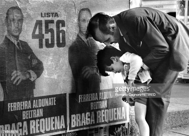 A man helps a small boy to relieve himself against a poster of politician Wilson Ferreira Aldunate Uraguay 1971