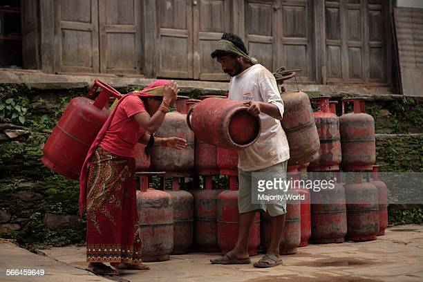 A man helps a woman to carry cylinders of Liquefied Petroleum Gas on her back at a neighbourhood in Bandipur Nepal June 25 2010 The country depends...