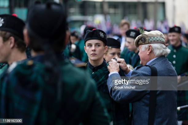 A man helps a young boy prepare for the ANZAC Day March on April 25 2019 in Sydney Australia Australians commemorating 104 years since the Australian...
