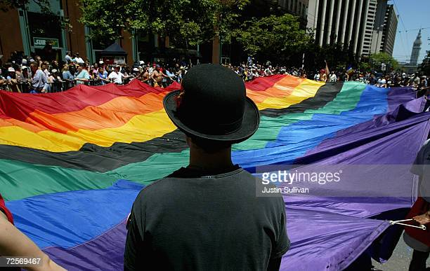 A man helps carry a large pride flag during the 2004 Pride Parade June 27 2004 in San Francisco Tens of thousands lined the streets of San Francisco...