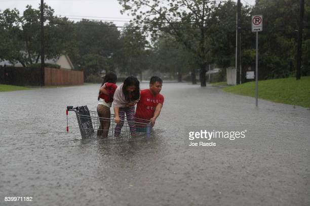A man helps children across a flooded street as they evacuate their home after the area was inundated with flooding from Hurricane Harvey on August...