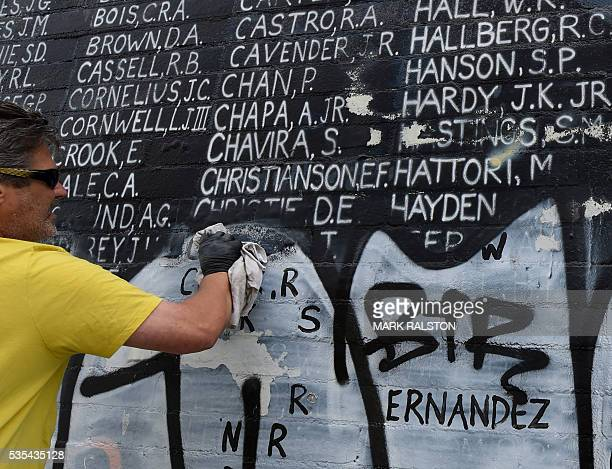 A man helps cleanup a Veterans Memorial containing the names of 2273 unaccounted and missing in action Vietnam war soldiers after vandals covered the...