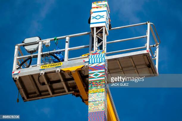 A man helps fix the top of a LEGO tower under construction in Tel Aviv on December 27 as the city attempts to break Guinness world record of the...