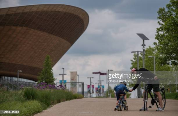 A man helps his son on to a bicycle in front of the Velodrome at Olympic Park as it is announced that Dame Tessa Jowell has died on May 13 2018 in...